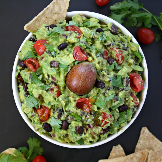 Bowl of fiesta guacamole with black beans and tomato