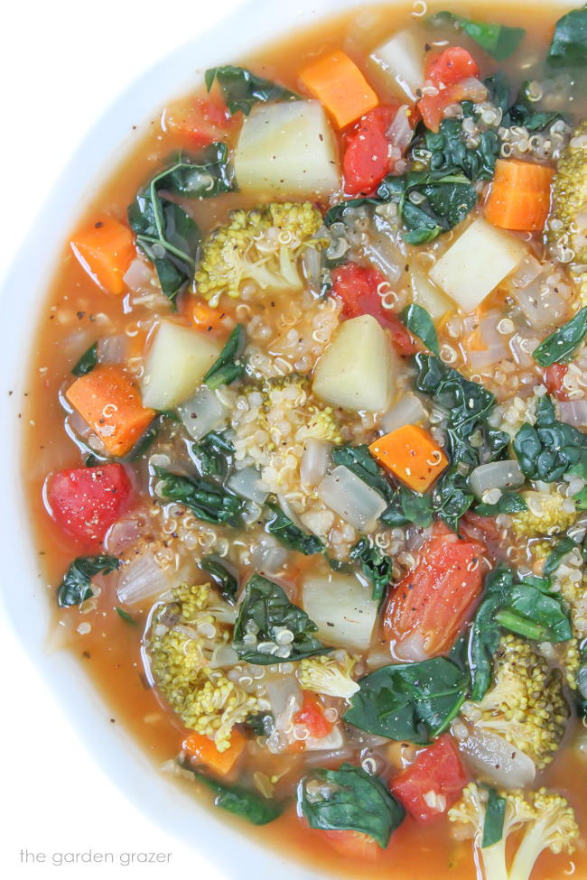 Vegan Quinoa Potato Soup with kale and spinach in a white bowl