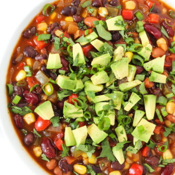 Three Bean Chili in a bowl topped with cilantro and avocado