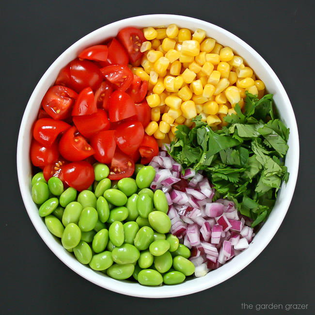 Ingredients for edamame tomato salad in a bowl