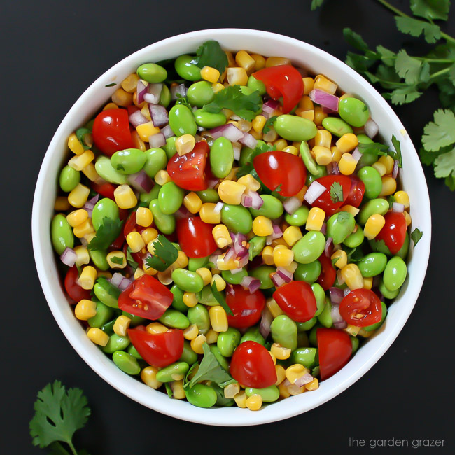 Lemony edamame corn salad tossed together in a bowl with tomato and cilantro