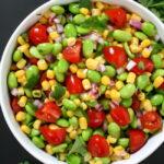 Bowl of edamame corn salad with tomato and cilantro