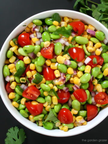 Bowl of edamame corn salad with tomato and cilantro