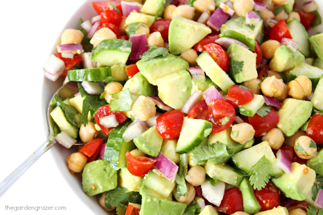 Avocado tomato salad in a bowl with spoon