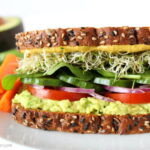 Avocado Sandwich on a plate with tomato, spinach, sprouts, and onion