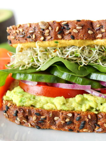 Vegan avocado sandwich with veggies and sprouts on a white plate
