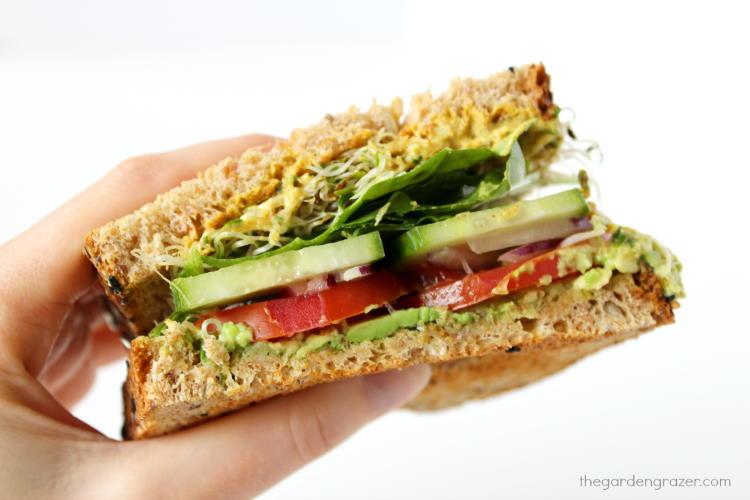 Hand holding up half of an avocado veggie sandwich