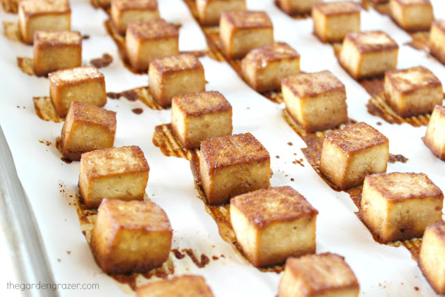 Tofu cubes spread out on a baking sheet