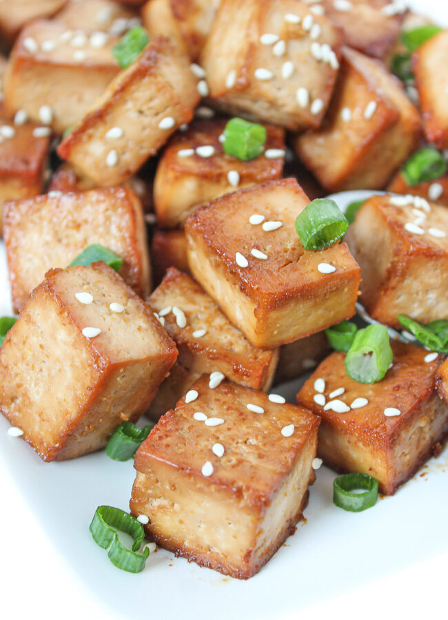 Cubes of easy baked marinated tofu on a plate with sesame seeds