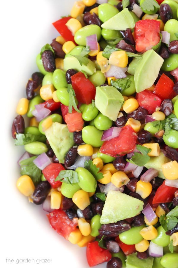 Avocado edamame salad with black beans and tomatoes in a bowl