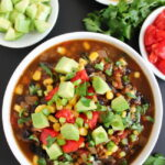 Bowl of black bean lentil taco soup with avocado, corn, and tomatoes