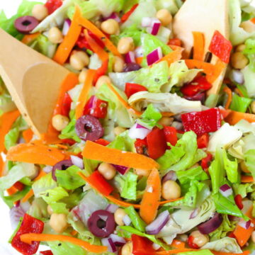 Vegan Italian Chopped Salad in a bowl with wooden utensils