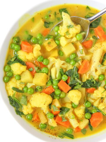 Bowl of vegan coconut curry soup with carrot, potato, and cauliflower