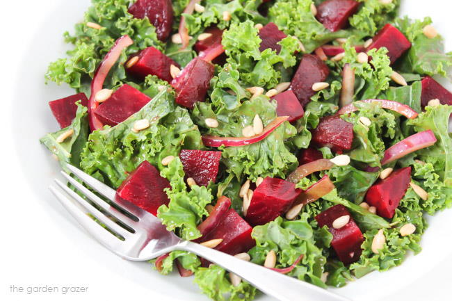Plate with kale salad with onions, beets, and sunflower seeds