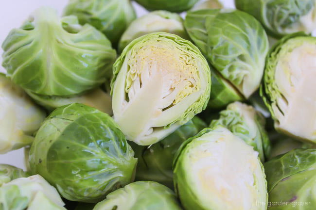 Raw Brussels sprouts cut in half on a cutting board