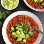 Bowls of smoky chipotle black bean chili with spoon and fresh avocado