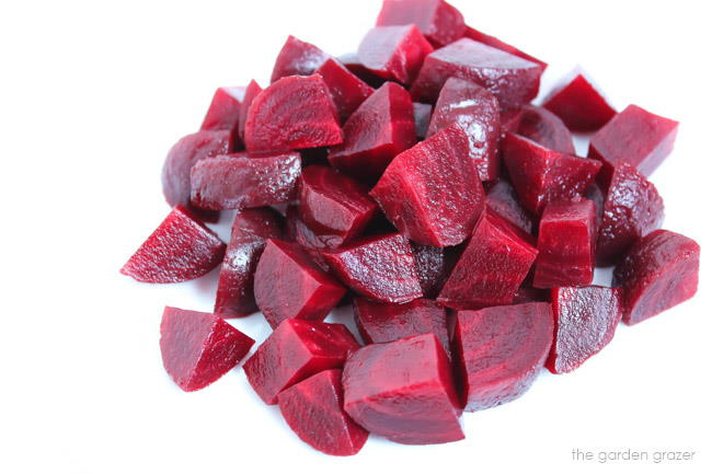 Roasted beets cut in chunks on a cutting board