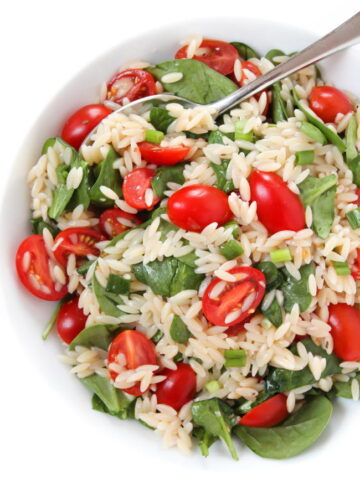 orzo tomato spinach salad in a bowl with spoon