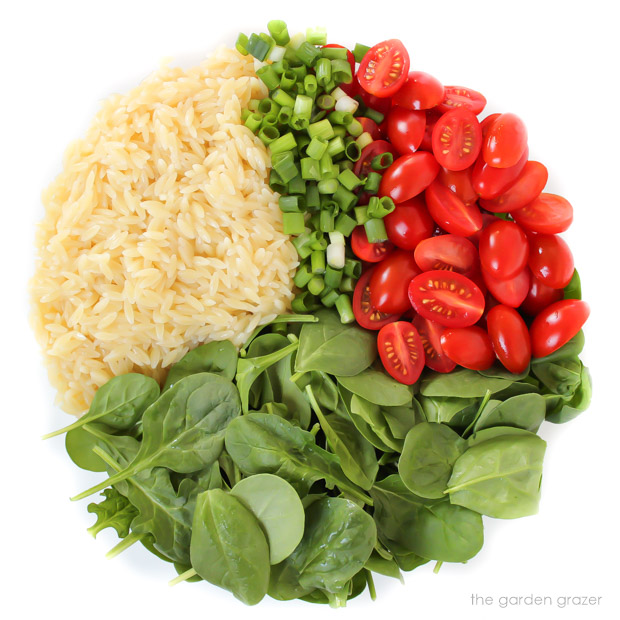 Ingredients for orzo tomato spinach salad in a bowl