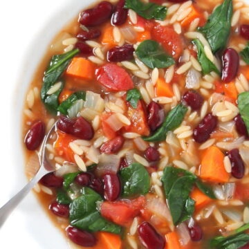 Bowl of kidney bean, orzo, spinach soup with a spoon