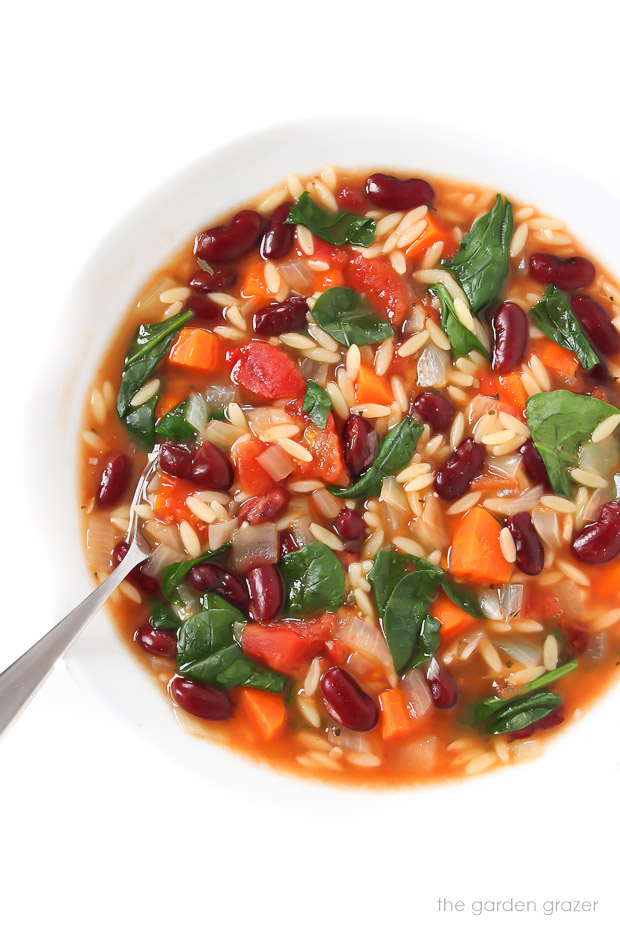 Bean orzo soup in a bowl with spoon