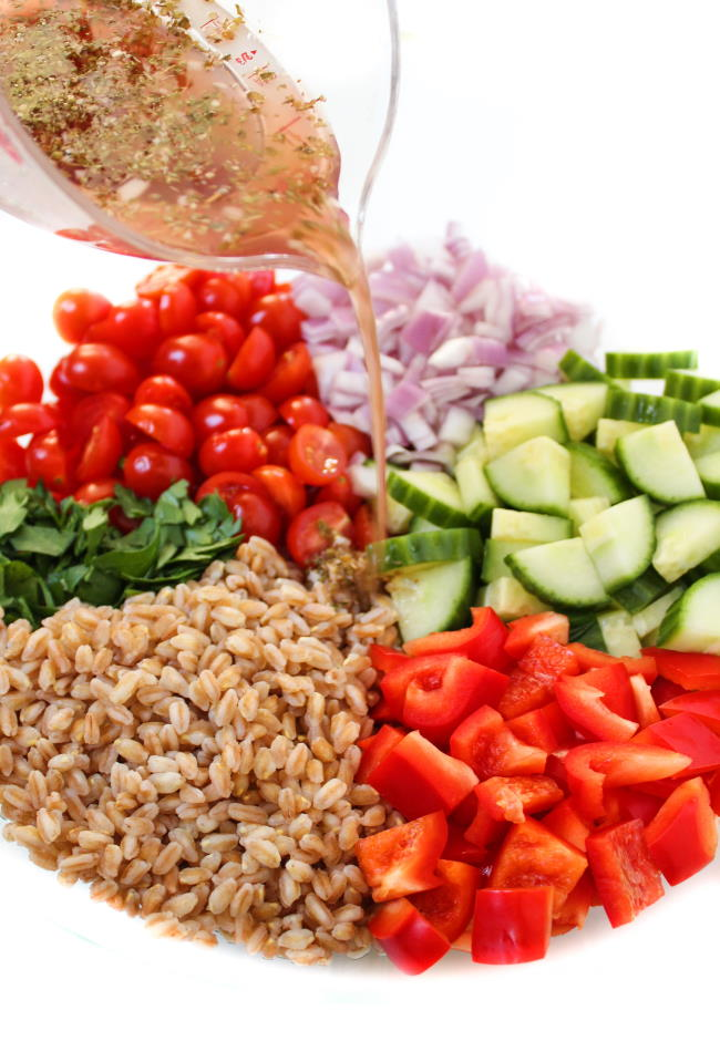 Ingredients in bowl for farro salad with dressing poured over top