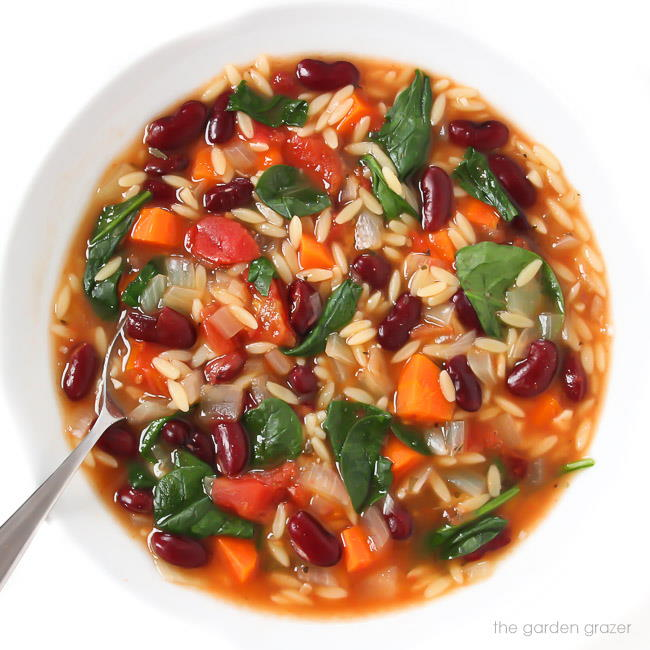 Kidney bean spinach soup in a bowl with spoon