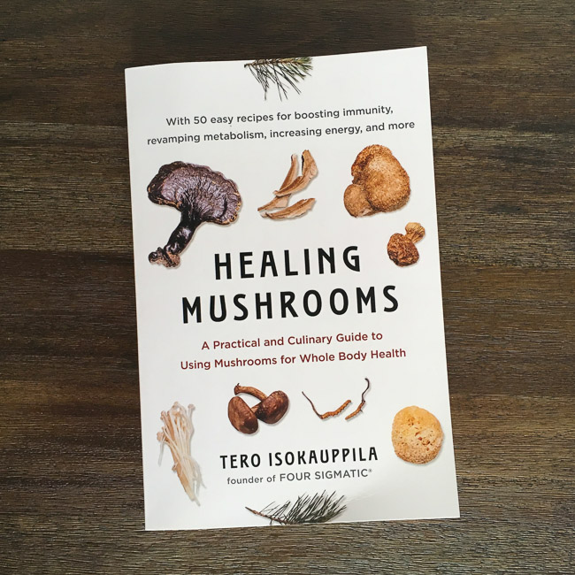 """Healing Mushrooms"" book by Tero Isokauppila on a wooden table"