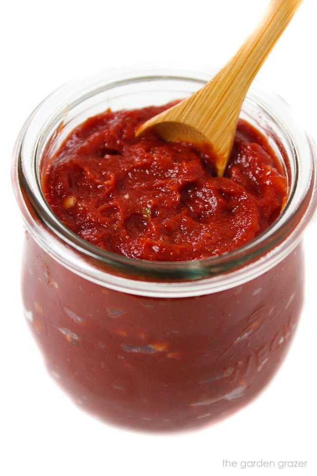Prepared homemade pizza sauce in a small jar with spoon