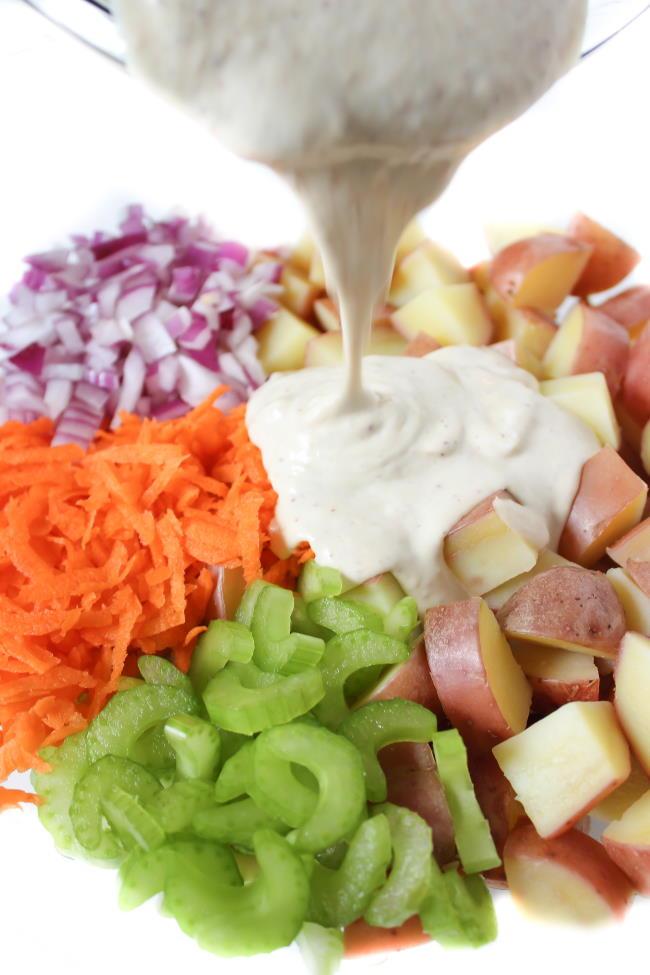 Vegan creamy dressing being poured on to potato salad