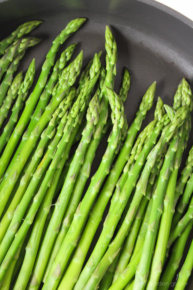 Fresh asparagus spears steaming in a pan on the stove