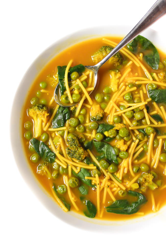 Healing turmeric noodle soup in a bowl with spoon