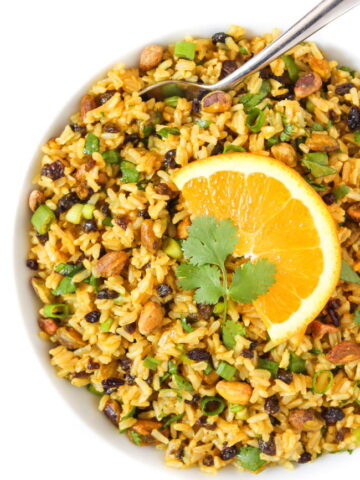 Curried Orange Rice Salad in a bowl with spoon