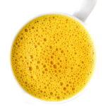 Bright yellow golden turmeric milk latte in a mug