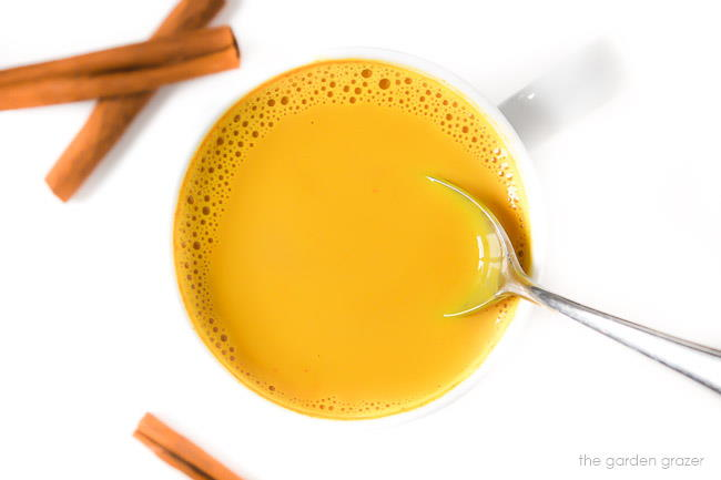 Mug of turmeric milk latte with cinnamon sticks and a spoon