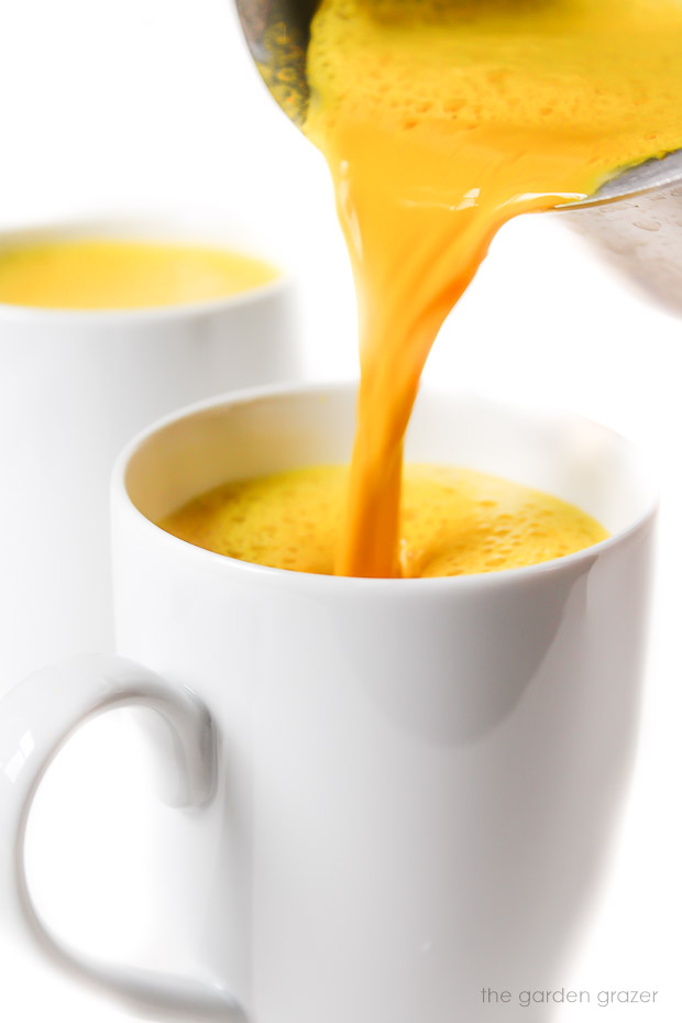 Pouring bedtime golden turmeric milk from saucepan to mug