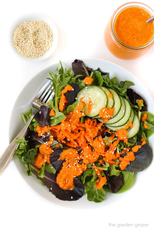 Carrot ginger dressing on a green salad in bowl