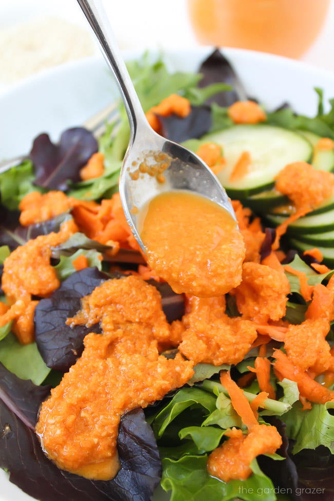 Close up of carrot ginger dressing being drizzled over lettuce with spoon