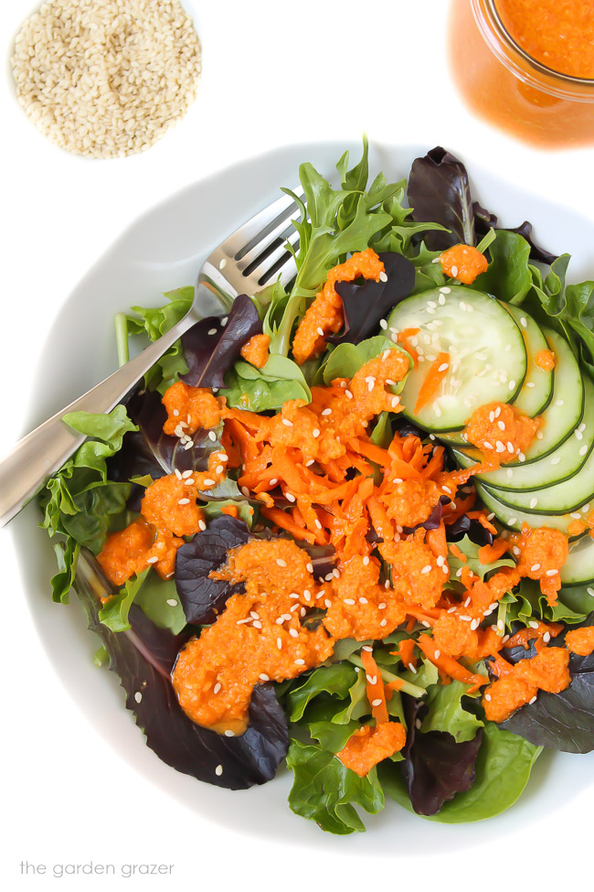 Green tossed salad in a bowl with carrot ginger dressing drizzled over top