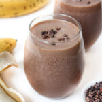 Two chunky monkey protein smoothies in a glass topped with cacao
