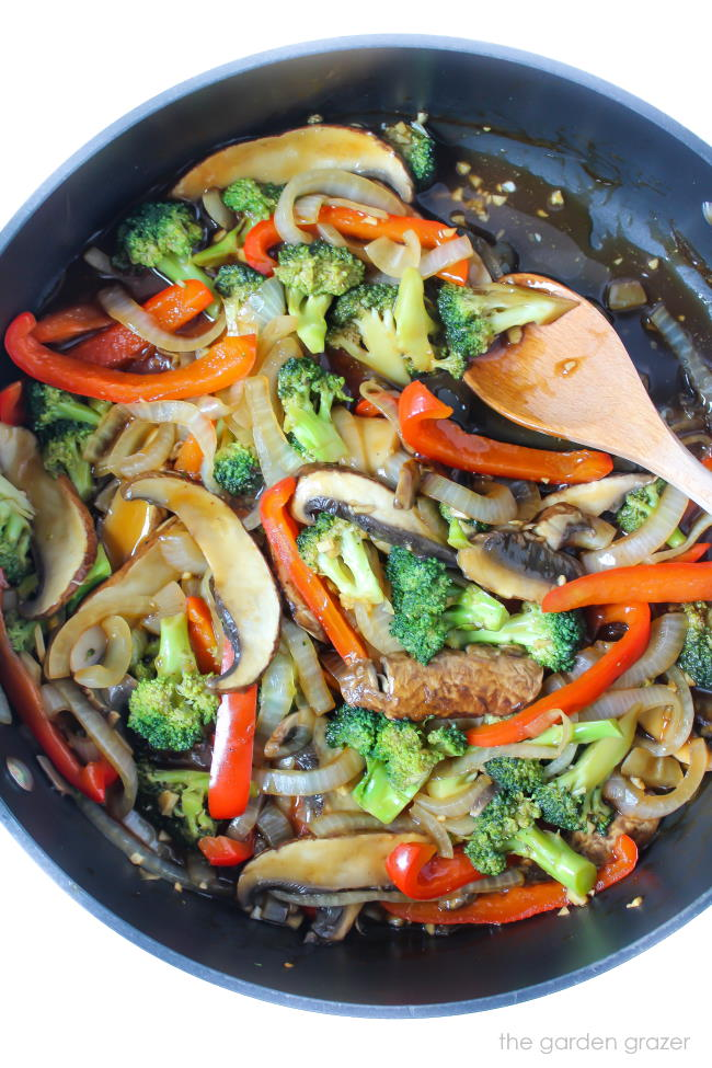 Cooked vegan stir fry in a pan with wooden spoon