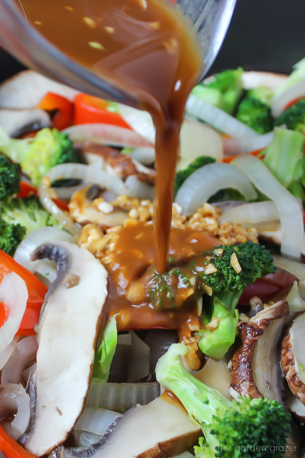 Stir fry sauce pouring over mushroom and veggies in pan