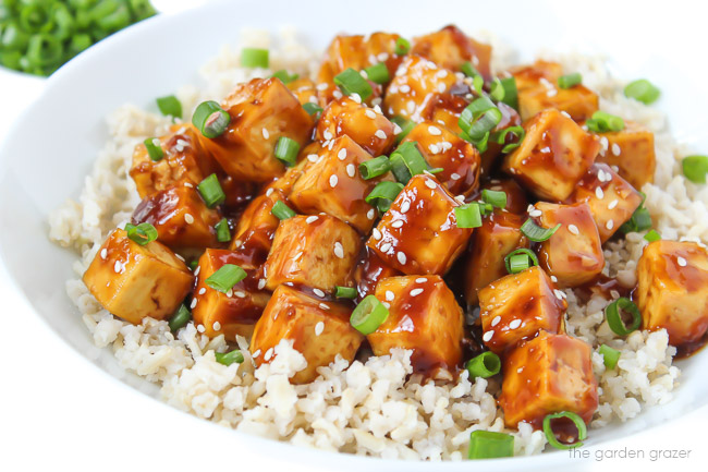 bowl of vegan teriyaki baked tofu topped with sesame seeds