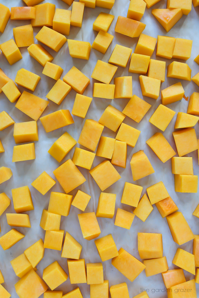 butternut squash cubes spread on a pan ready to roast
