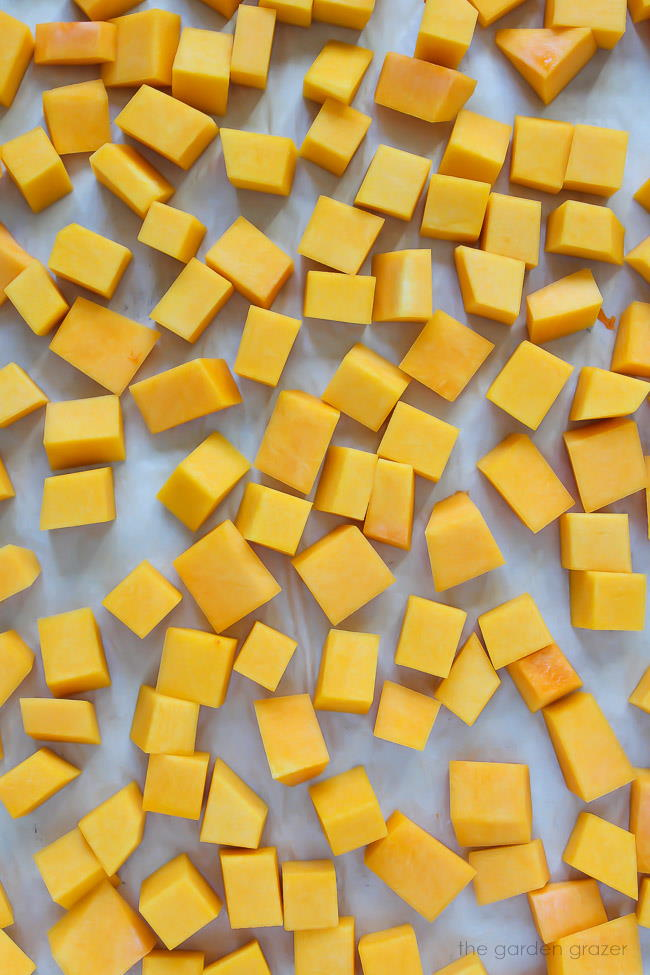 Raw butternut squash cubes spread on a pan ready to roast