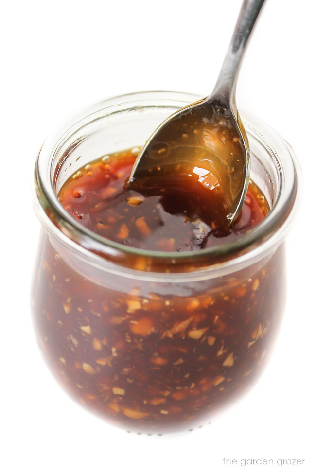 Glass jar with homemade teriyaki sauce and spoon