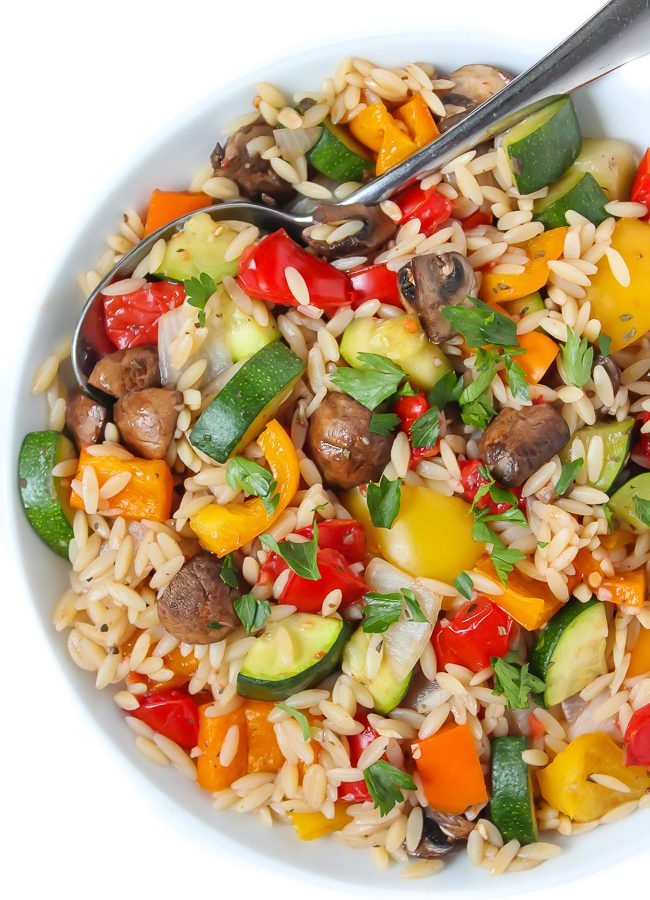 Bowl of roasted vegetable orzo tossed in garlic-balsamic dressing with spoon