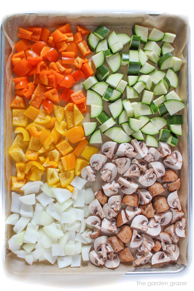 Assortment of raw, diced vegetables on a baking pan