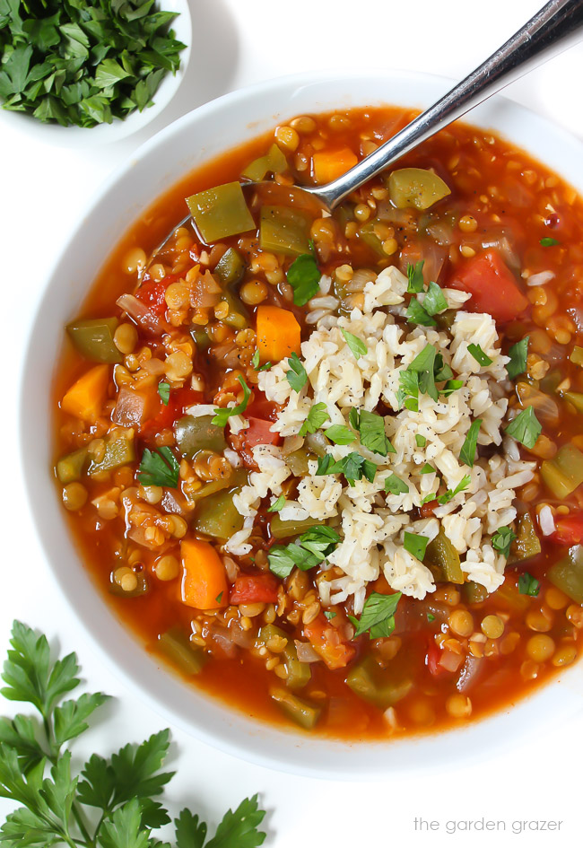 Bowl of stuffed pepper lentil soup topped with brown rice and parsley