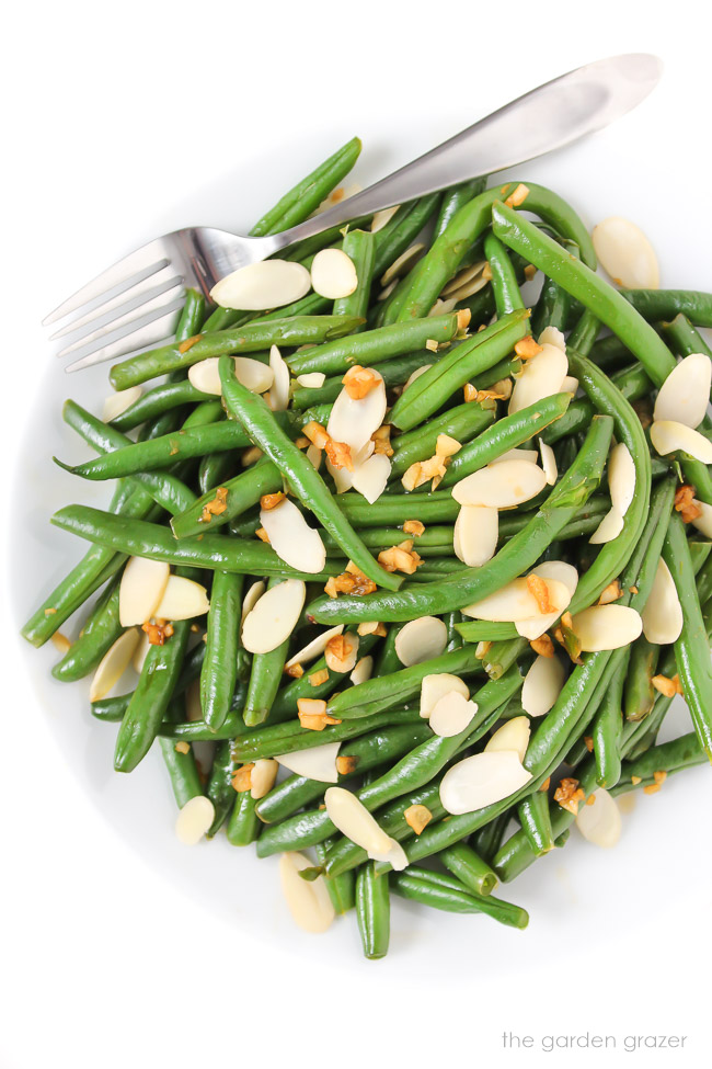 Garlic green beans on a plate sprinkled with sliced almonds
